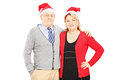 Smiling mature couple with santa hats hugging isolated on white background Royalty Free Stock Photography