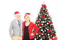 Smiling mature couple with santa hats posing in front of a chris christmas tree isolated on white background Stock Image