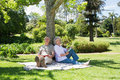 Smiling mature couple sitting against tree at park portrait of a a the Royalty Free Stock Photos