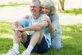 Smiling mature couple sitting on grass at park portrait of a the Royalty Free Stock Image
