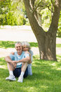Smiling mature couple sitting on grass at park portrait of a the Royalty Free Stock Photography