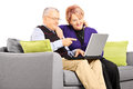 Smiling mature couple sitting on a sofa and looking at laptop isolated white background Stock Image