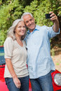 Smiling mature couple taking pictures of themselves leaning against their cabriolet Royalty Free Stock Images