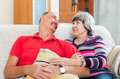 Smiling mature couple together on sofa Stock Photo