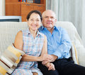 Smiling mature couple together on sofa in home Stock Photos