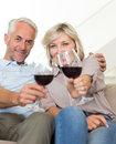 Smiling mature couple with wine glasses sitting on sofa portrait of a at home Stock Photos