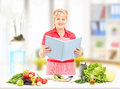 Smiling mature female cooker with book of recipies preparing sal apron and salad Royalty Free Stock Images