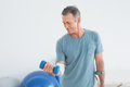 Smiling mature man with crutch and dumbbell at the gym hospital Stock Images