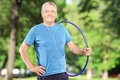 Smiling mature man with headphones holding a hula hoop in park Royalty Free Stock Photography
