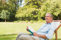 Smiling mature man holding a book and looking up in deck chair in the park Royalty Free Stock Photos