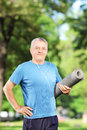 Smiling mature man holding an exercising mat and posing in park Royalty Free Stock Photography