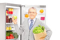 Smiling mature man holding a paper bag next to a refrigerator full of products and looking at camera isolated on white background Stock Photos