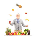 A smiling mature man juggling fruits behind a table full with fr and vegetables isolated on white background Royalty Free Stock Image