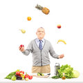 A smiling mature man juggling fruits behind a table full with ingredient isolated on white background Royalty Free Stock Photo