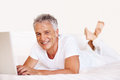 Smiling mature man with laptop on bed Royalty Free Stock Image