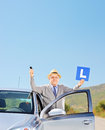 Smiling mature man posing next to his car holding a l sign and k key after having driver s licence outside shot with tilt Royalty Free Stock Image