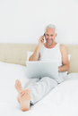 Smiling mature man using cellphone and laptop in bed casual at home Royalty Free Stock Photography