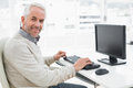 Smiling mature man using computer at desk in office side view of a a bright Royalty Free Stock Photos