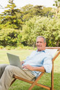 Smiling mature man using laptop and at camera Stock Photos