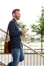 Smiling mature man walking down the stairs with mobile phone Royalty Free Stock Photo