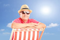 Smiling mature man wearing hat and sunglasses posing on a beach chair sunny day Stock Image