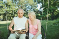 Smiling mature man and woman 65-69 years old reading a book in