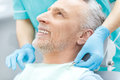 Smiling mature patient and dentist in medical gloves Royalty Free Stock Photo