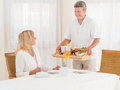 Smiling mature senior husband serving his wife healthy breakfast middle aged matured as she sits at the table as he arrives with a Royalty Free Stock Image