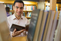 Smiling mature student with book by shelf in library close up portrait of a the Stock Photos