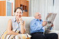 Smiling mature woman and elderly man with newspaper women men in home interior Stock Photography