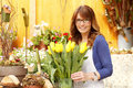 Smiling mature woman florist small business flower shop owner shallow focus Stock Images