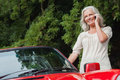 Smiling mature woman having phone call standing by her cabriolet Royalty Free Stock Image