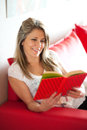 Smiling mature woman reading book on sofa Royalty Free Stock Photo