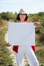 Smiling mature woman showing blank sign for teasing in countryside