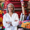 Smiling mature woman standing by textiles in her fabric shop Royalty Free Stock Photo
