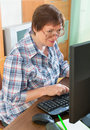 Smiling mature woman using keyboard sitting in front of pc and Stock Photography