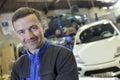 Smiling mechanic in car garage Royalty Free Stock Photo