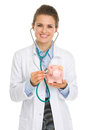 Smiling medical doctor woman listening piggy bank stethoscope Stock Photography