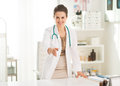 Smiling medical doctor woman in office stretching hand for handshake Stock Photo