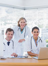 Smiling medical staff working on a laptop and a computer in their office Royalty Free Stock Photos