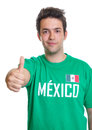 Smiling mexican sports fan showing thumb up from mexico with a green jersey on an isolated white background Royalty Free Stock Photo