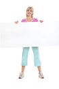 Smiling middle age woman holding blank billboard Stock Images