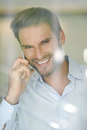 Smiling middle aged business man on a phone looking through the window successful businessman handsome Stock Photo