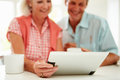 Smiling middle aged couple looking at digital tablet home Royalty Free Stock Image