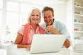 Smiling middle aged couple looking at laptop home sitting down table Royalty Free Stock Photography