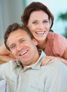 Smiling middle aged couple relaxing at home Stock Photos