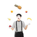 A smiling mime artist juggling fruits isolated against white background Stock Photography