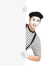 Smiling mime artist posing behind a blank panel isolated on white background Stock Photos