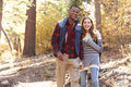 Smiling mixed race couple hike in a forest holding hands Royalty Free Stock Photo