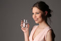Smiling model with glass of water. Close up. Gray background Royalty Free Stock Photo